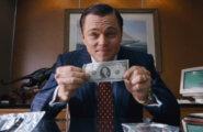 Волк с Уолл-стрит держит в руках доллары